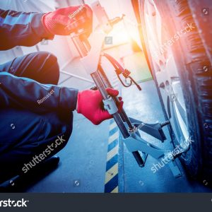 stock-photo-car-mechanic-installing-sensor-during-suspension-adjustment-wheel-alignment-work-at-repair-service-618149720